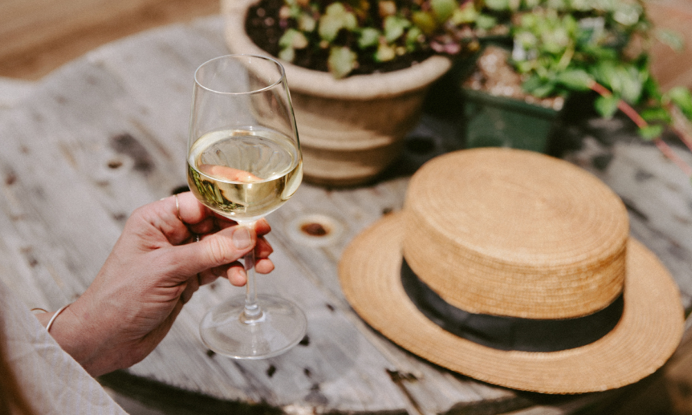 a glass of white Bordeaux in a man's hand with a hat in the background